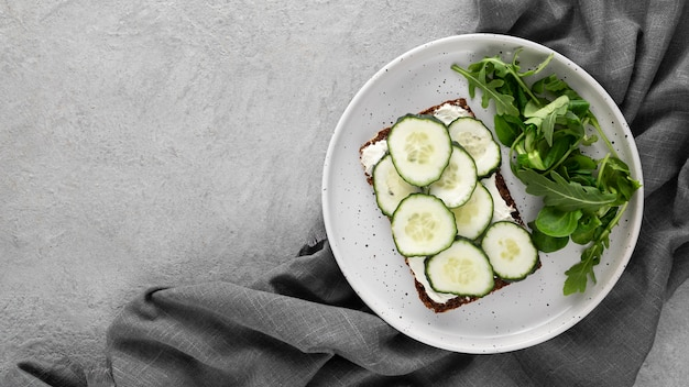 Sanduíche de vista superior com pepinos no prato e pano de prato