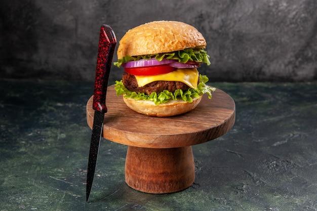 Sanduíche delicioso e garfo vermelho em uma placa de madeira em uma superfície de cor escura com espaço livre