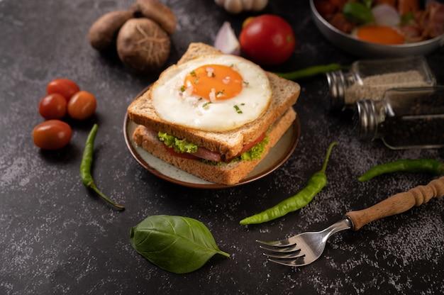 Sanduíche do café da manhã feito com pão, ovo estrelado, presunto e alface.
