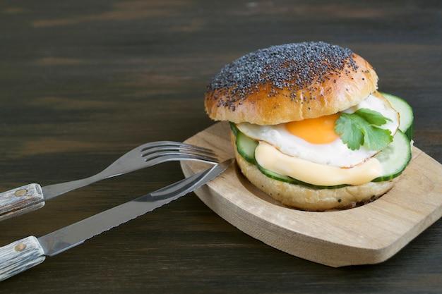 Sanduíche do ovo e do pepino no fundo de madeira.