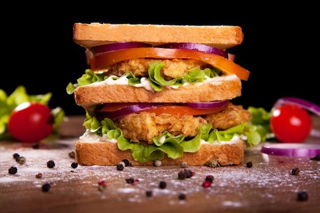 Sanduíche duplo, com frango, alface, tomate, cebola, pimenta e molho, sobre uma mesa de madeira e fundo preto.