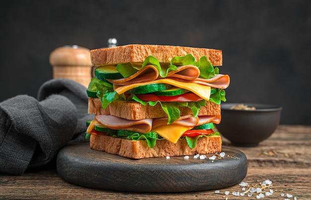 Sanduíche duplo com presunto, queijo e vegetais frescos em uma placa de madeira sobre um fundo marrom