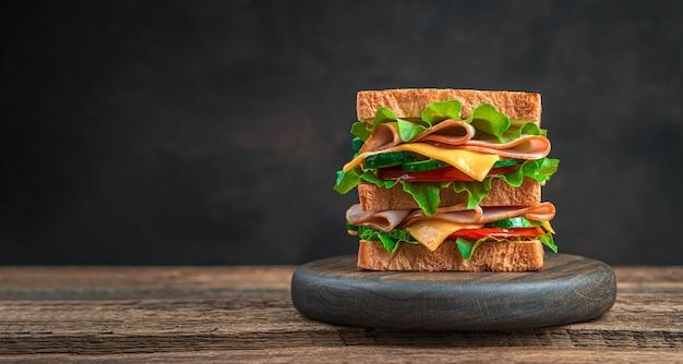 Sanduíche duplo com presunto, queijo, vegetais frescos e ervas em um fundo marrom com um espaço de cópia