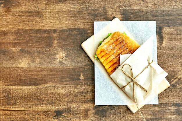Sanduíche em um envelope, amarrado com corda a uma mesa de madeira