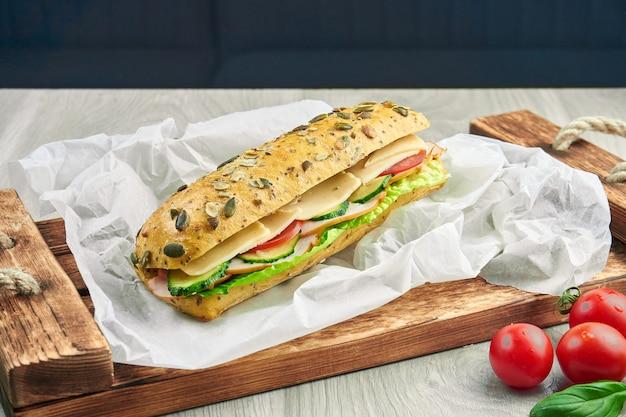 Sanduíche em um pão ciabatta com frango, tomate, pepino, queijo e alface em uma bandeja de madeira. fechar-se. saborosa comida rápida