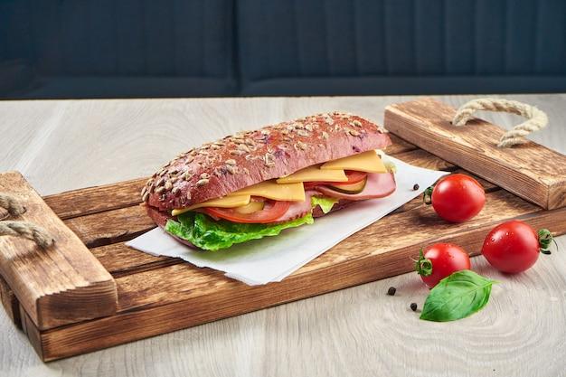 Sanduíche em um pão ciabatta com presunto, tomate, queijo pepino em conserva e alface em uma bandeja de madeira. fechar-se. saborosa comida rápida