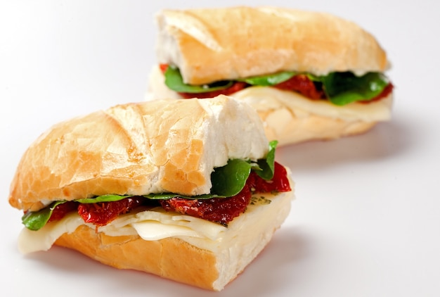 Sanduíche em um prato branco com peito de peru, tomate, alface e queijo na mesa