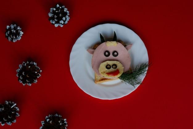 Sanduíche engraçado com o símbolo comestível da vaca touro de 2021, feito de torrada de salsicha e queijo
