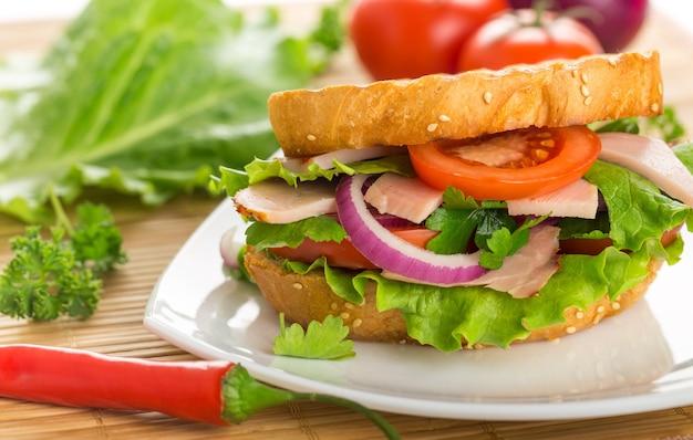 Sanduíche fresco com presunto e legumes na mesa de madeira