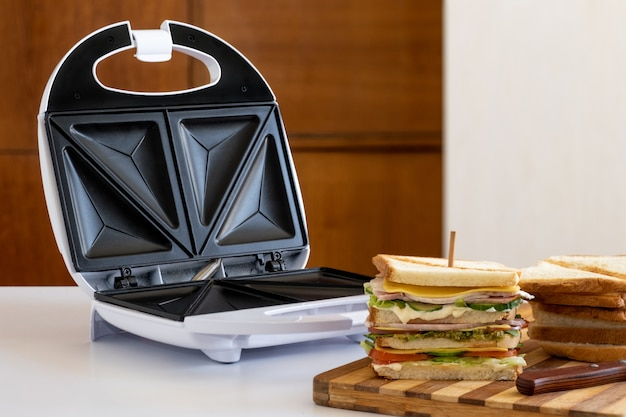 Sanduíche fresco com queijo, ervas, tomate, pepino e bacon na mesa de madeira com pão.