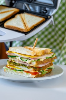 Sanduíche fresco com queijo, ervas, tomate, pepino e bacon no fundo da torradeira