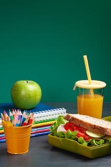 Sanduíche fresco e maçã para almoço saudável na lancheira de plástico