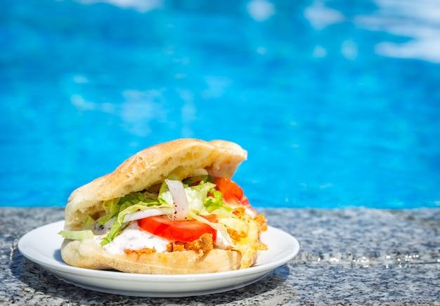 Sanduíche fresco em um prato perto da piscina