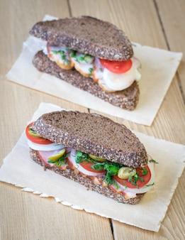 Sanduíche fresco em uma mesa de madeira com um pedaço de estopa.