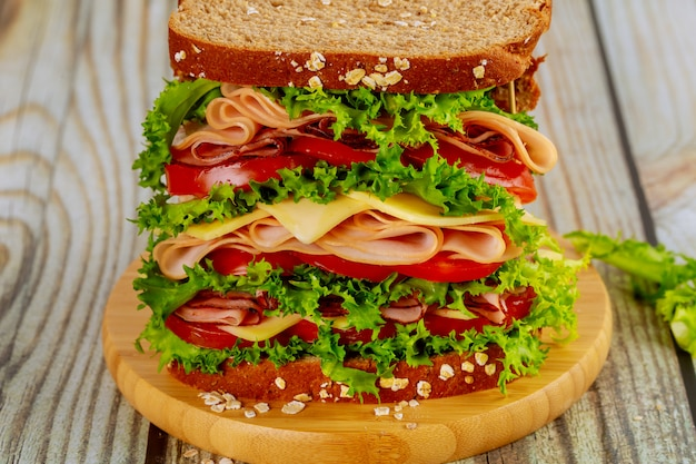 Sanduíche grande colorido com presunto, queijo e legumes.