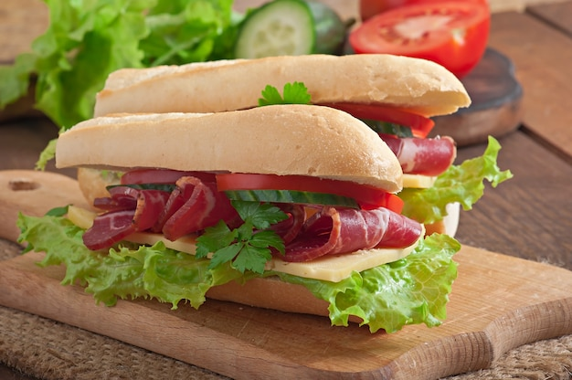 Sanduíche grande com carne defumada crua numa superfície de madeira