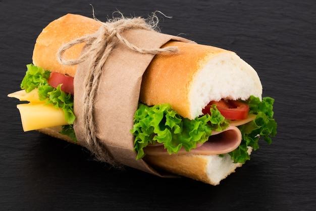 Sanduíche grande com carne e queijo no escuro.