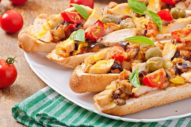 Sanduíche grande com legumes assados (abobrinha, berinjela, tomate) e frango com queijo e manjericão em fundo de madeira velho