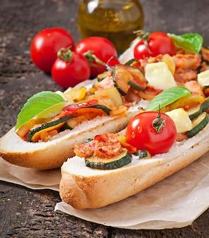 Sanduíche grande com legumes assados com queijo e manjericão na superfície de madeira velha