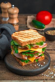 Sanduíche grande com pão grelhado, queijo fiambre e legumes frescos em um fundo de madeira
