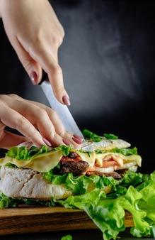 Sanduíche grande em fundo preto comida de rua, fast food. hambúrgueres caseiros com carne, queijo na mesa de madeira. imagem tonificada. chef corta uma faca de sanduíche