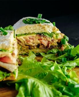 Sanduíche grande, fast food. hambúrgueres caseiros com carne, queijo em cima da mesa de madeira. imagem enfraquecida. sanduíche em um corte