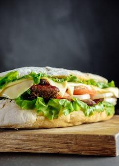 Sanduíche grande, fast food. hambúrgueres caseiros com carne, queijo em cima da mesa de madeira. imagem enfraquecida.