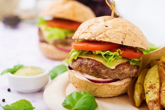 Sanduíche grande - hambúrguer com hambúrguer de carne suculenta, queijo, tomate e cebola roxa e batata frita.