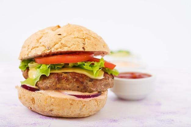 Sanduíche grande - hambúrguer com hambúrguer de carne suculenta, queijo, tomate e cebola vermelha na mesa de luz e batatas fritas.