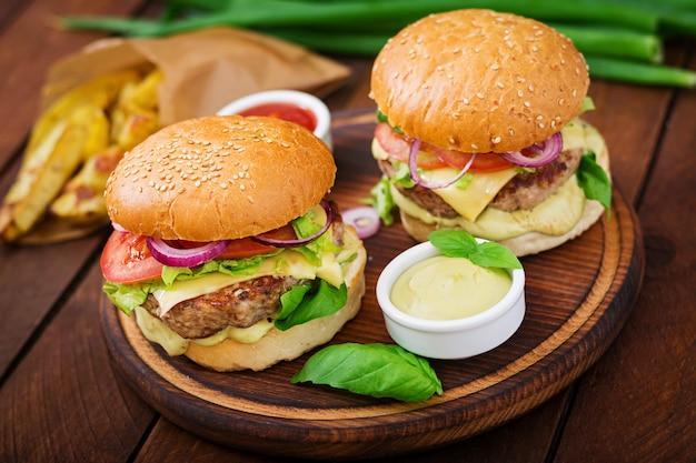 Sanduíche grande - hambúrguer com hambúrguer de carne suculenta, queijo, tomate e cebola vermelha na mesa de madeira