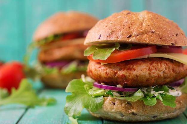 Sanduíche grande - hambúrguer com hambúrguer de frango suculento, queijo, tomate e cebola vermelha na mesa de madeira