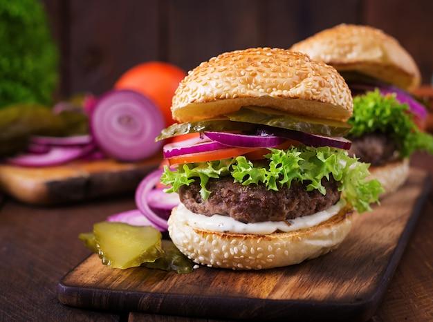 Sanduíche grande - hambúrguer de hambúrguer com carne, picles, tomate e molho tártaro em fundo de madeira.