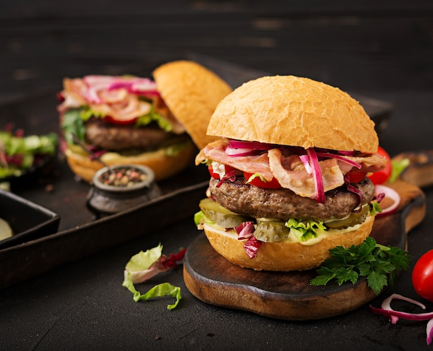Sanduíche grande - hamburguer hamburguer com carne, tomate, pepino em conserva e bacon frito.