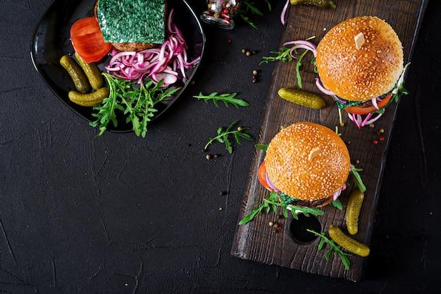 Sanduíche grande - hambúrguer hambúrguer com carne, tomate, queijo manjericão e rúcula. vista do topo. configuração plana