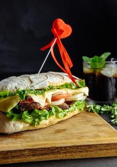 Sanduíche grande para casal apaixonado em placa de madeira de pepino alecrim fundo preto comida de rua, fast food. hambúrgueres caseiros com carne, queijo na mesa de madeira. copo de coca-cola com gelo, hortelã
