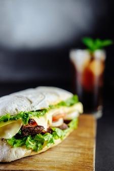 Sanduíche grande para casal na placa de madeira de pepino alecrim fundo preto comida de rua, fast food. hambúrgueres caseiros com carne, queijo na mesa de madeira. copo de coca-cola com gelo, hortelã