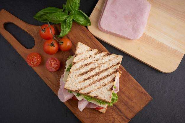Sanduíche grelhado com presunto, queijo, tomate e alface servido numa tábua de madeira.