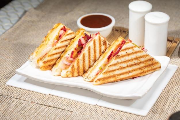 Sanduíche grelhado com vegetais de queijo grelha torrada vista superior do item do café da manhã no fundo do branco da placa. saboroso vegetal com queijo vegetariano com sanduíche de chutney verde