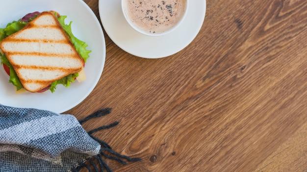 Sanduíche grelhado e xícara de café na mesa de madeira