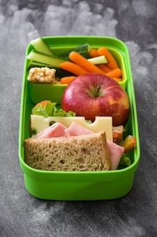 Sanduíche, legumes e frutas na ardósia