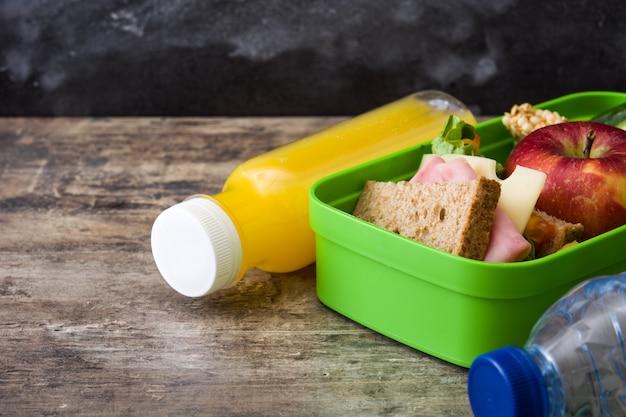 Sanduíche, legumes e frutas na mesa de madeira