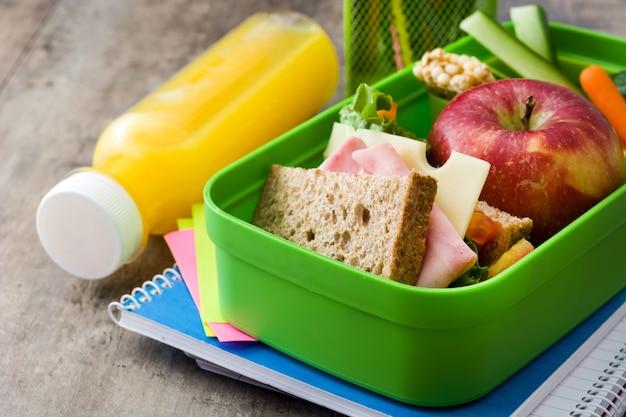 Sanduíche, legumes, frutas e suco na mesa de madeira