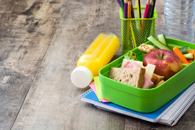Sanduíche, legumes, frutas e suco no espaço da cópia de mesa de madeira