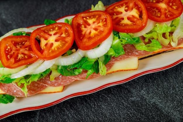 Sanduíche longo com queijo muenster, salame e vegetais.