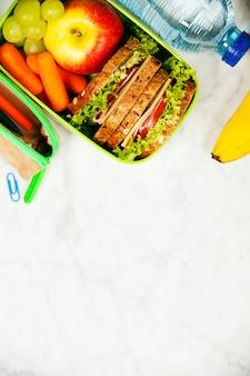 Sanduíche, maçã, uva, cenoura, artigos de papelaria e garrafa de água o