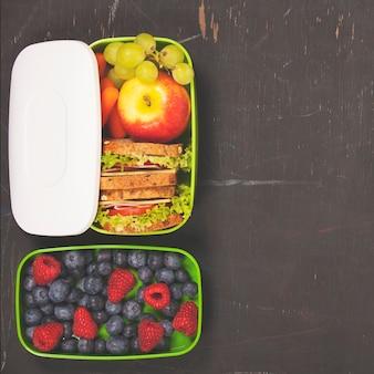 Sanduíche, maçã, uva, cenoura, bagas em lancheira de plástico eb