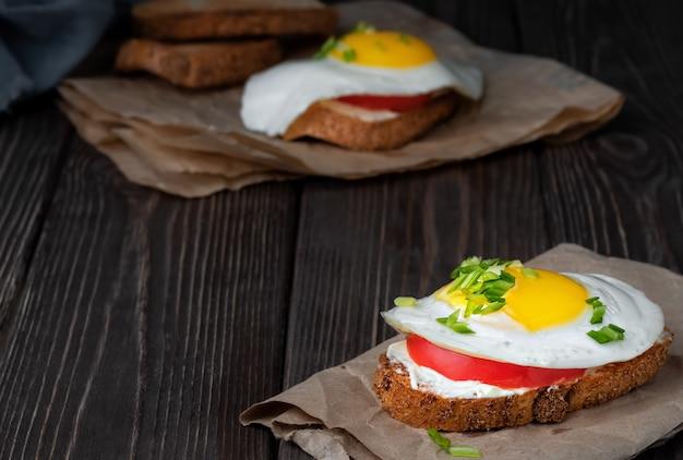 Sanduíche na torrada com cream cheese, uma fatia de tomate e um ovo frito