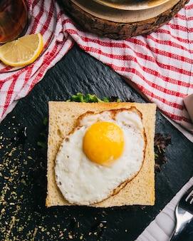 Sanduíche no café da manhã com ovo frito na parte superior.