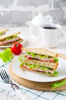 Sanduíche no café da manhã com tomates recheados com presunto e alface em uma superfície de madeira clara. foco seletivo.