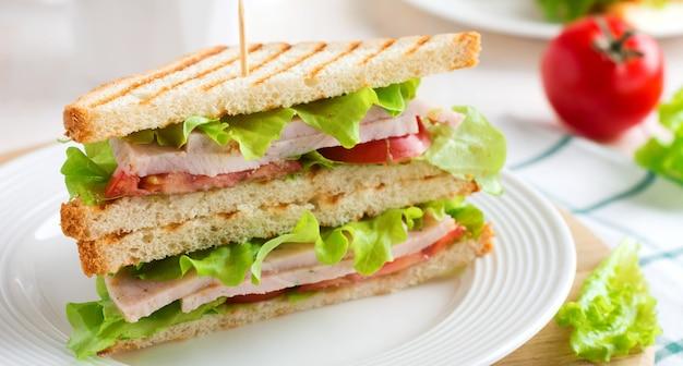 Sanduíche no café da manhã com tomates recheados com presunto e alface sobre um fundo claro de madeira. foco seletivo.
